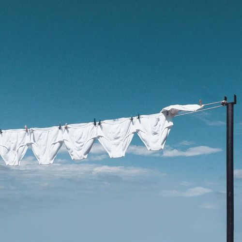 Low angle view of white underwear hanging on clothesline