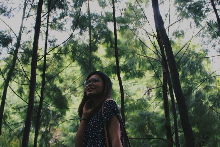 Young woman standing by trees in forest