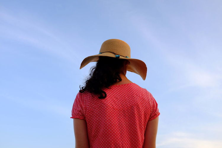 Black Black Hair Blue Blue Sky Casual Clothing Clear Sky Colorful Day Dress Hair Hat Low Angle View Outdoors Part Of Red Red Dress Sky Standing Woman Woman Against Sky Young Young Women