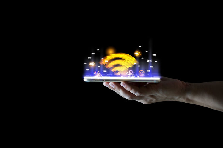 Close-up of hand holding smart phone over black background