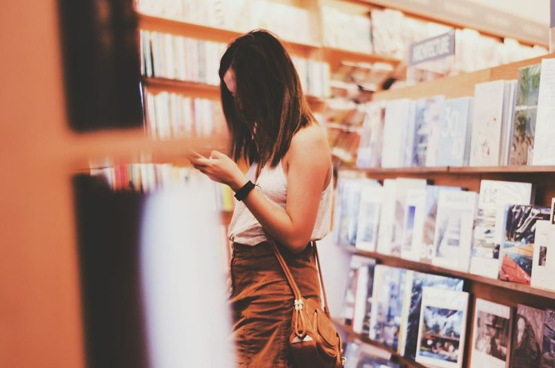 Side view of woman using mobile phone while standing amidst bookshelves at store