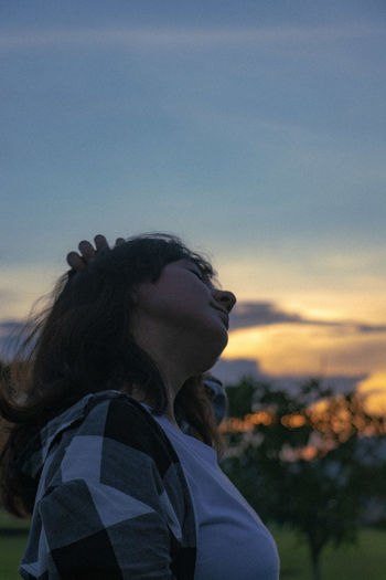 Young woman stretching against sky during sunset