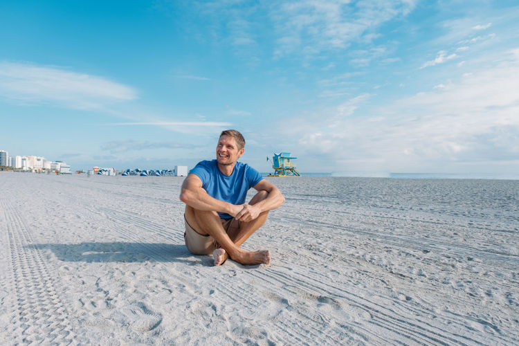 Guy walking along  miami beach. happy handsome man tourist in casual clothes sitting on sandy beach.