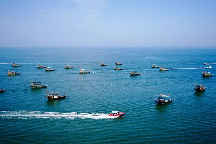 High angle view of boats sailing in sea against clear sky