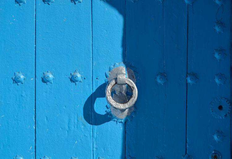 Close-up of knocker on blue door