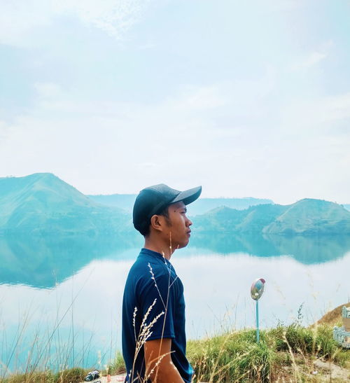 Side view of man standing by lake against mountains and sky