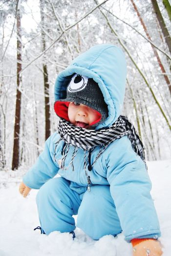 Low angle view of child in snow against trees