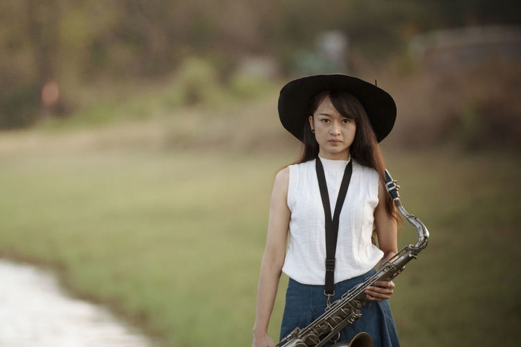 Woman with saxophone with nature background Woman Saxophone Playing