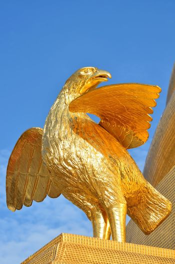 Low angle view of golden eagle statue at temple against sky