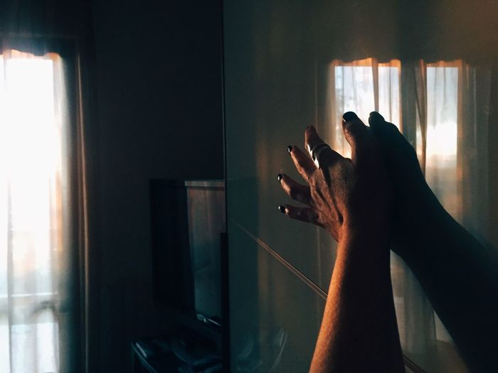 Close-up of hand touching window at home