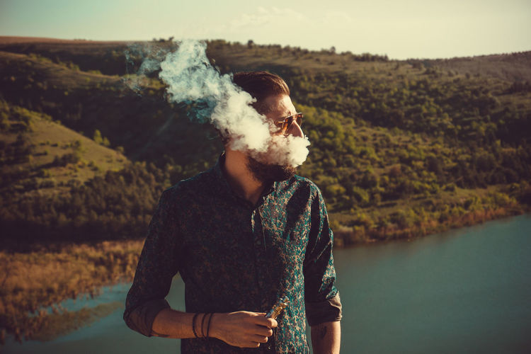 Man smoking while standing by lake