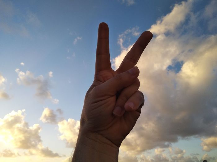 Low angle view of person hand gesturing peace sign against sky