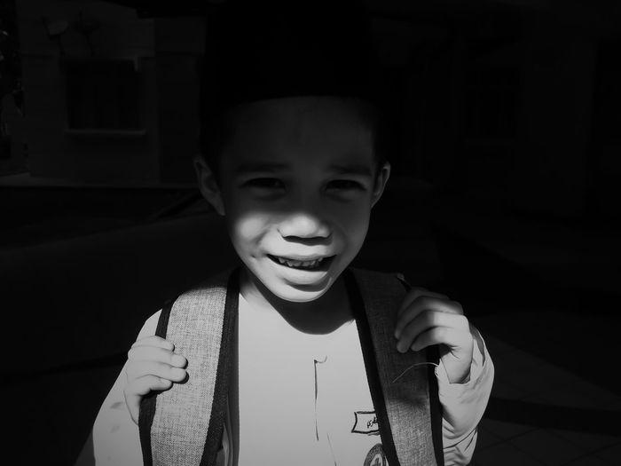 Portrait Of Boy With Backpack Standing In Darkroom