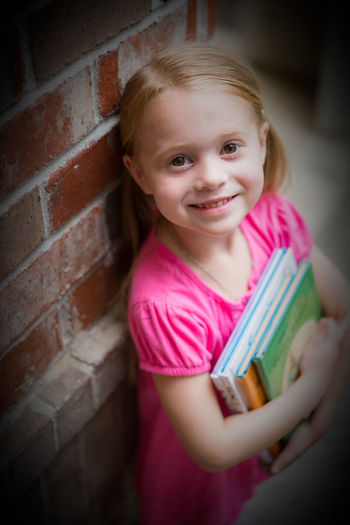 Portrait Of Smiling Girl Holding Books By Brick Wall