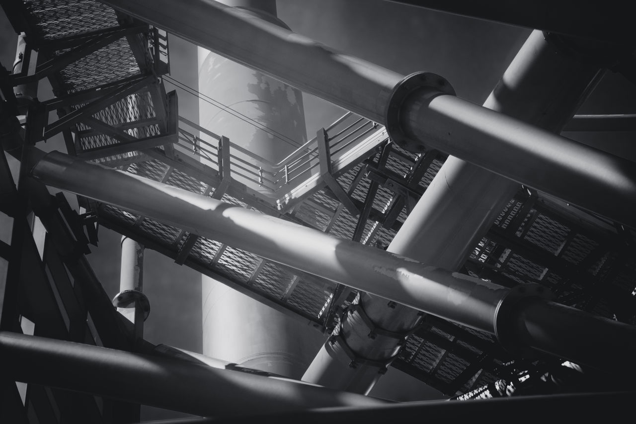 metal, low angle view, no people, railing, close-up, connection, day, pipe - tube, indoors, pipeline, architecture, technology, equipment, staircase, built structure, transportation, steps and staircases, electricity, steel, power supply, silver colored