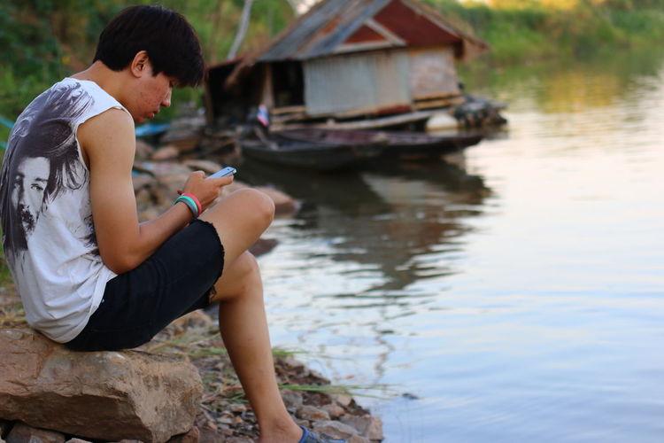 Mekong River NongKhai,ThaiLand Architecture Casual Clothing Country Life Countryside Day Focus On Foreground Full Length Lake Leisure Activity Lifestyles Nature One Person Outdoors Real People Side View Sitting Still Still Life Water Young Adult Young Men Young Women