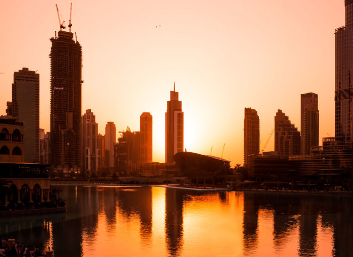 Buildings by river against sky during sunset