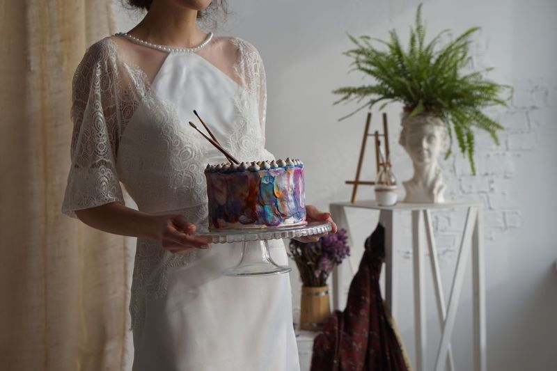 Midsection of woman with cake standing at home
