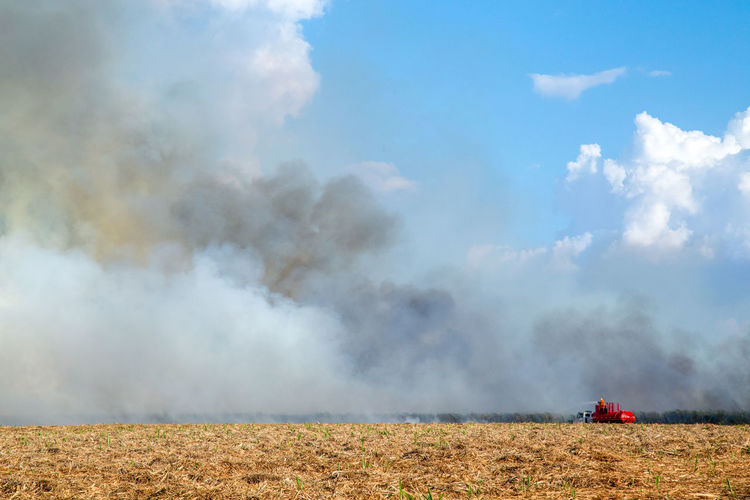 Fired Agricultural Equipment Agricultural Machinery Agriculture Beauty In Nature Cloud - Sky Day Dust Environment Environmental Issues Farm Field Land Land Vehicle Landscape Mode Of Transportation Nature No People Outdoors Pollution Rural Scene Sky Smoke - Physical Structure Sugar Cane Field Transportation
