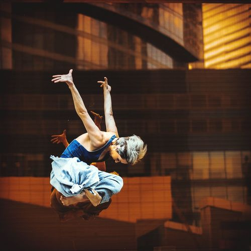 Full Length Of Young Woman Jumping Against Buildings