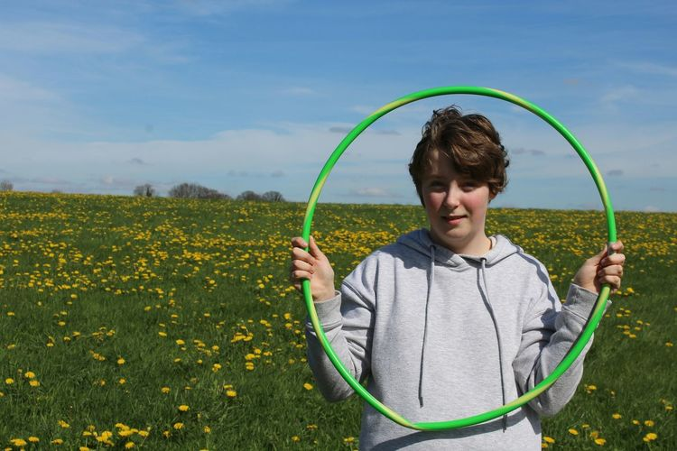 Portrait Of Girl Holding Hula Hoop While Standing On Field Against Sky