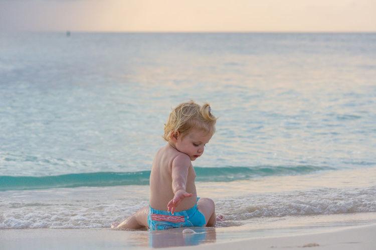 Shirtless boy sitting on shore at beach