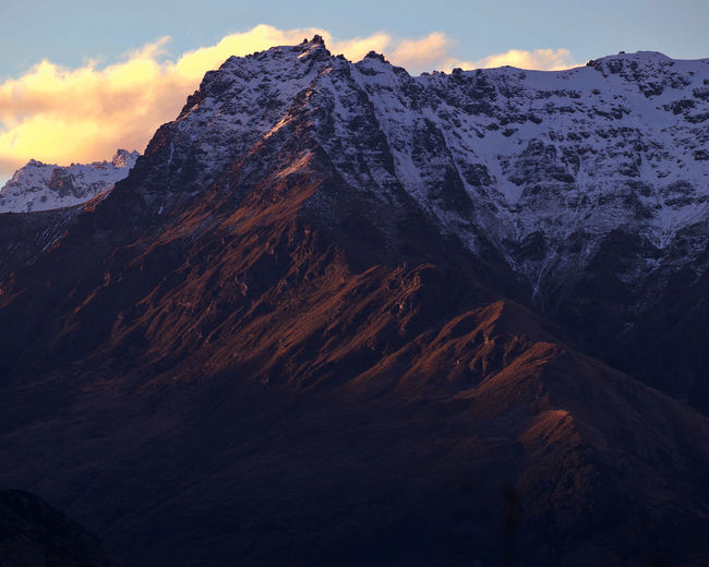 Scenic view of snowcapped mountains against sky during sunset. queenstown, new zealand