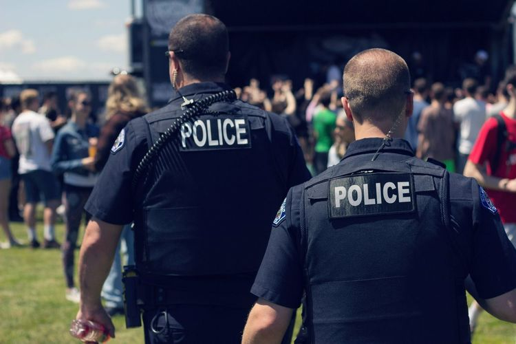 Rear View Of Police Force At Park