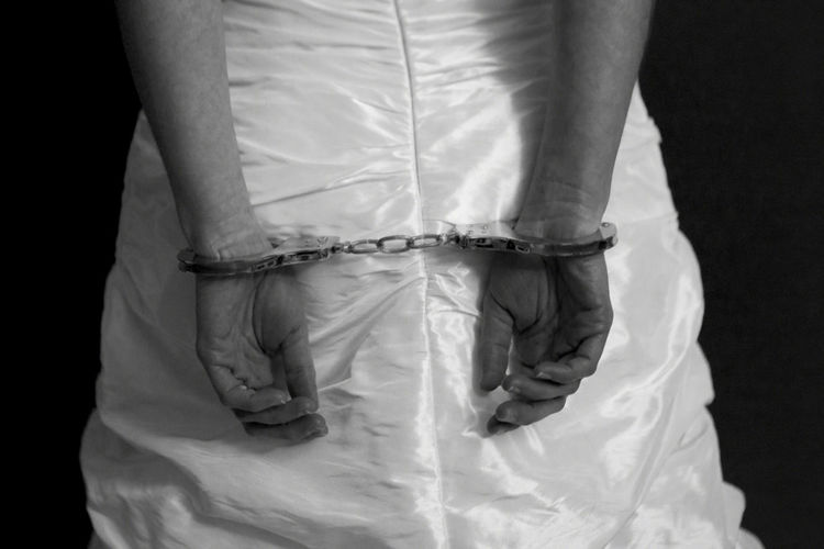 Midsection of woman with handcuffs wearing wedding dress