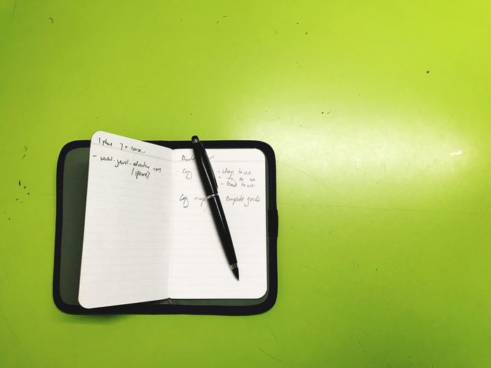 High angle view of diary and pen on green table
