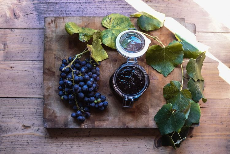 High Angle View Of Fresh Blueberries And Preserves On Cutting Board