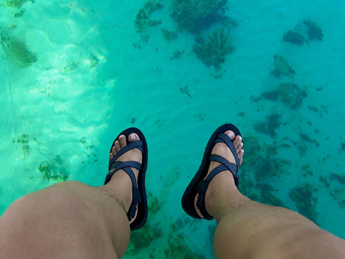 Low Section Of Man Wearing Sandals Over Sea