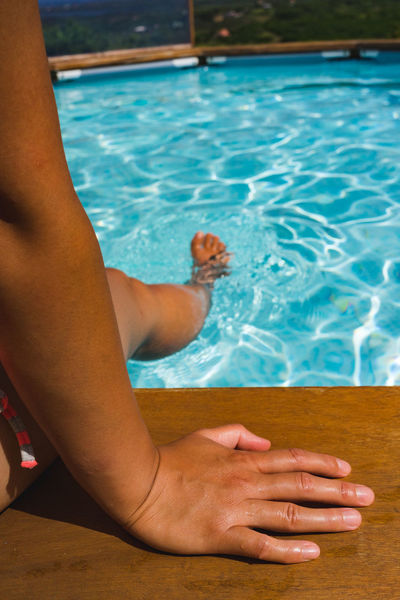 Women arms detail. Sitting on the pool. Adult barefoot Adult Body Part Day Hand Human Body Part Human Foot Human Leg Human Limb Leisure Activity Lifestyles Low Section Nature One Person Pool Poolside Real People Relaxation Swimming Pool Water Women