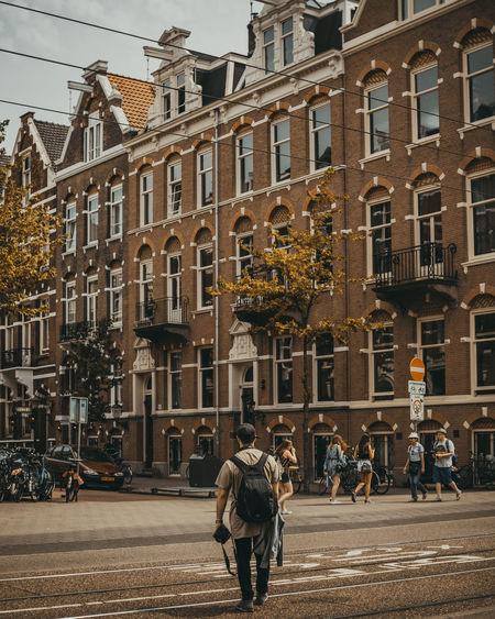 People walking on road against buildings in city