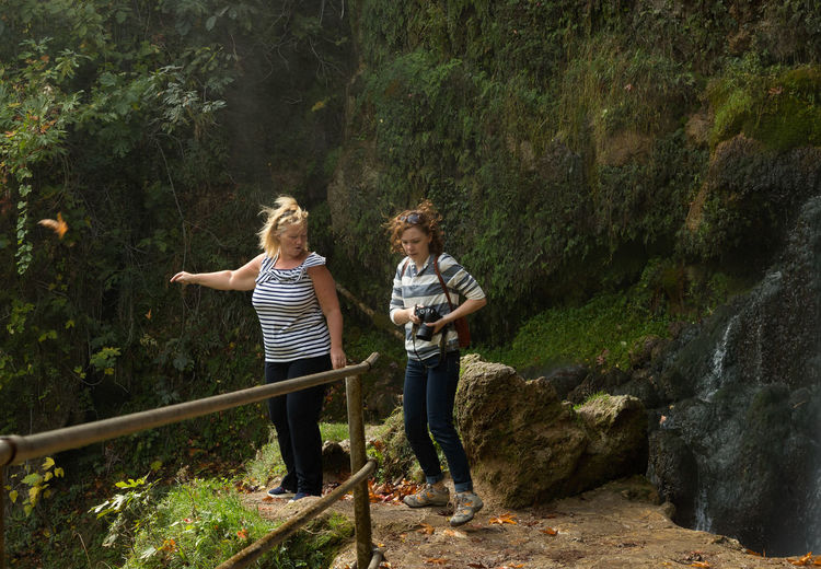 Full length of female friends standing by rock formations