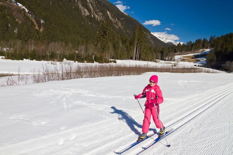 Full length portrait of cute little girl enjoying cross-country skiing