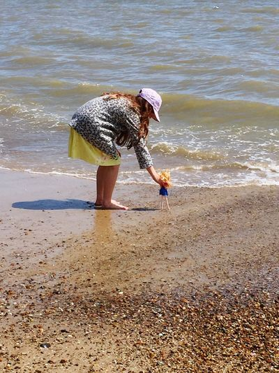 Side View Of Girl Playing With Doll While Standing On Shore At Beach