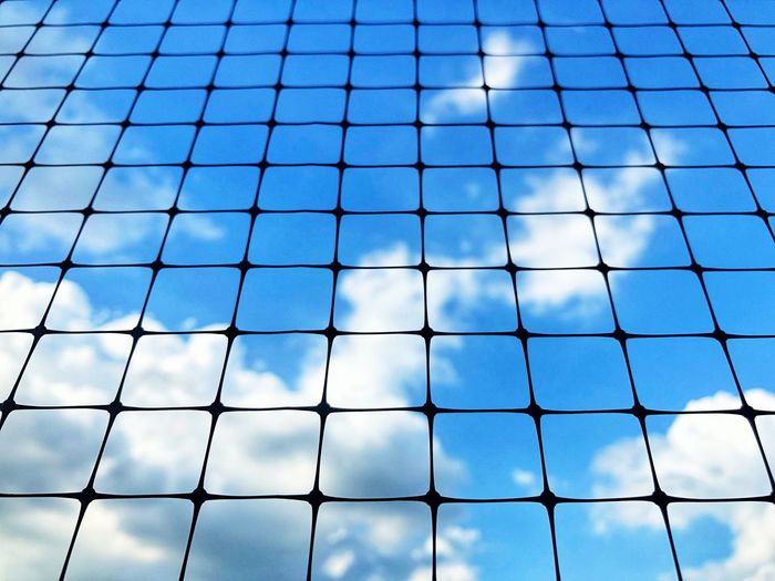 Blue sky with clouds behind black net. Blue Cloud - Sky Freedom Frame Pattern No People Backgrounds Fence Full Frame Day Low Angle View Nature Outdoors Boundary Chainlink Fence Sky Protection Net - Sports Equipment Security Safety Blue Grid