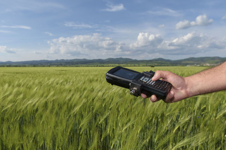 Human hand holding controller and wheat field. Geodesy Agriculture Field GPS Industry Wheat Working Agricultural Land Controller Engineer Field Geodesy Holding Horizon Human Hand Internet Keyboard Land Surveyor Location Measurement Network Outdoors Point Professional Occupation Receiver Wireless Technology