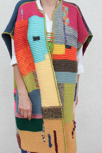 Midsection of woman holding multi colored umbrella