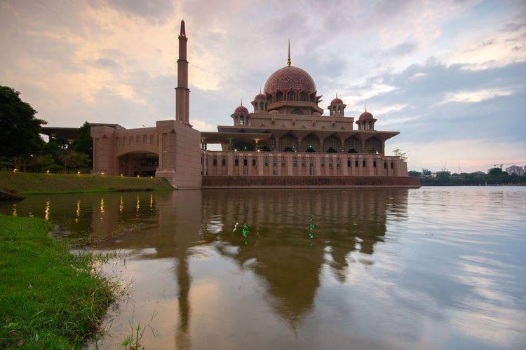 Putra mosque by lake against sky in city
