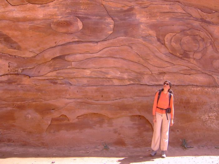 Full length of a woman standing by rock