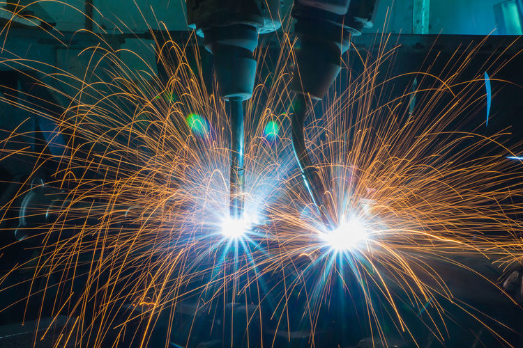 Automation welding mechanical procedure.,Industrial Robot arm active in factory Automobile Construction Industry LINE Machine Mechanical Modern Plant Transportation Welding Arm Auto Automation Automotive Blurred Motion Equipment Factory Illuminated Long Exposure Motion Part Sparks Steel Technology
