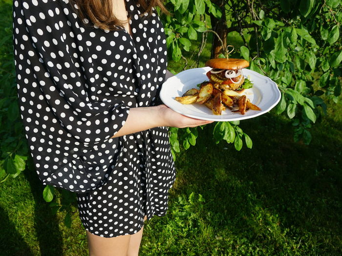 young woman wearing polkadotted dress holding a plate with cheeseburger CheeseBurger Hamburger BBQ Garden Summer Summer Party Party Garden Party Dress Fashion Unrecognizable Person Young Women Women Plate Low Section Standing Tree Food And Drink Ready-to-eat Indulgence Served Polka Dot Temptation