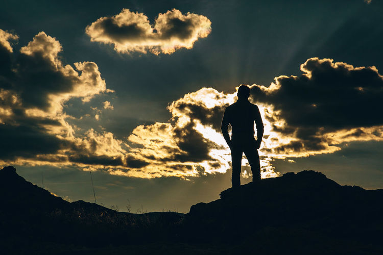 Rear view of silhouette mid adult man standing on mountain against sky during sunset