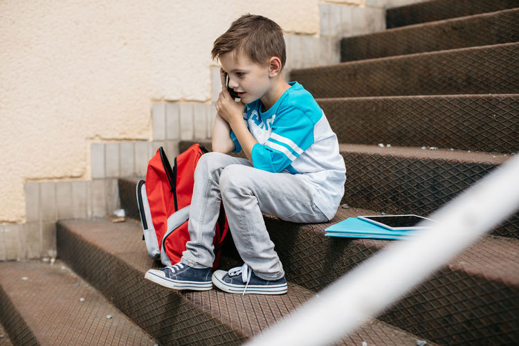 Full length of boy talking on mobile phone while sitting on steps