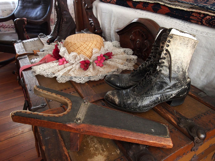 High Angle View Of Hat Amidst Antique Boots On Treasure Chest