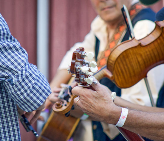 Annual Fiddlers' Convention & Festival 2014 Communication Connection Fiddle Focus On Foreground Group Hands Holding Jam Session Mandolin Music Brings Us Together Music Festival Musical Instruments Person Tuning Pegs Wrist Bands
