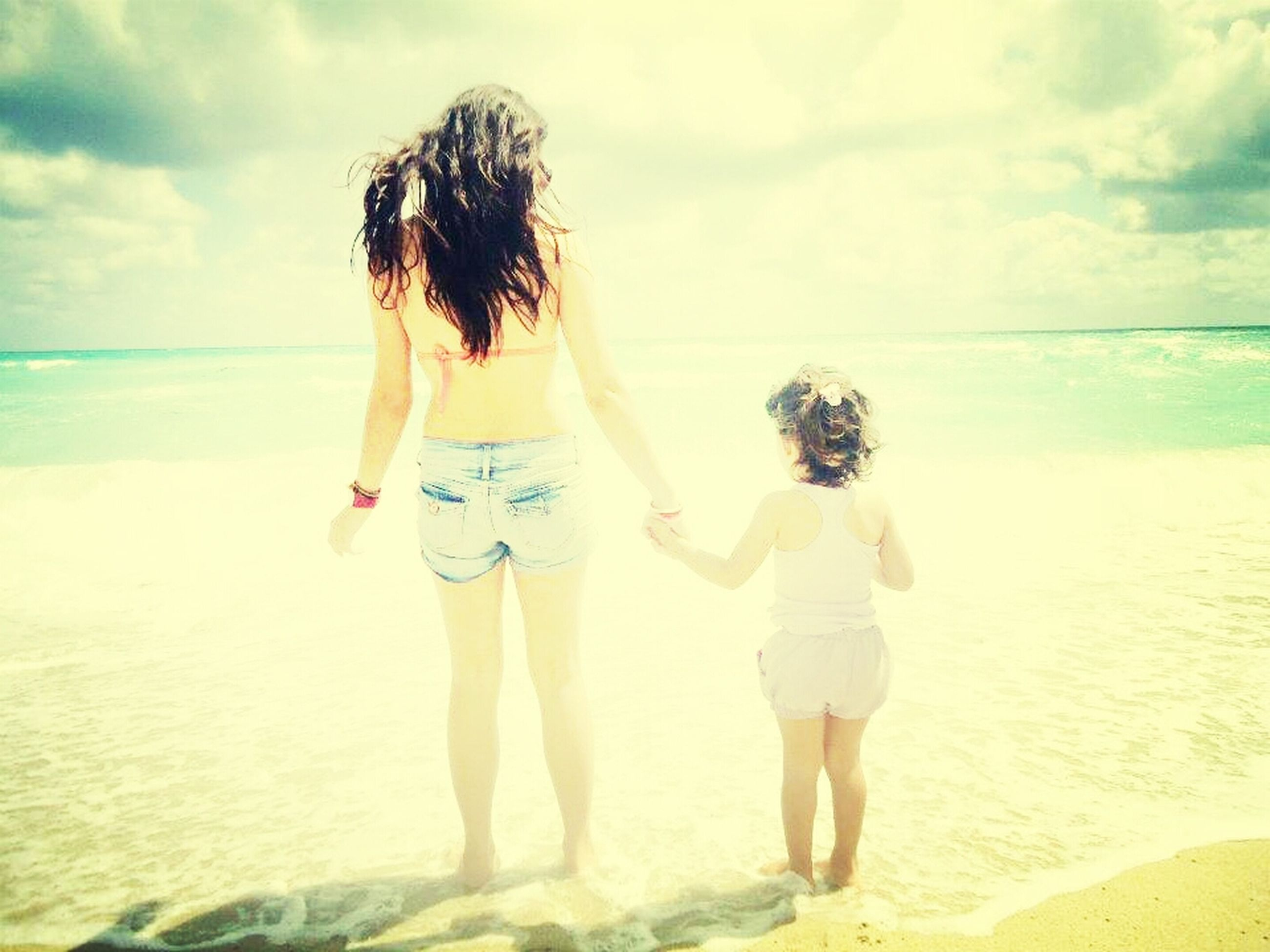 beach, sea, horizon over water, lifestyles, water, leisure activity, sky, shore, rear view, sand, vacations, full length, standing, person, togetherness, casual clothing, beauty in nature, bonding