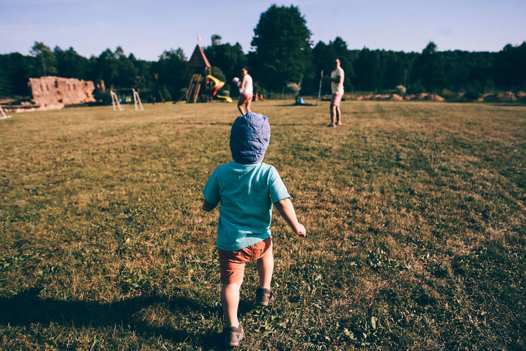 Rear view of children playing on field
